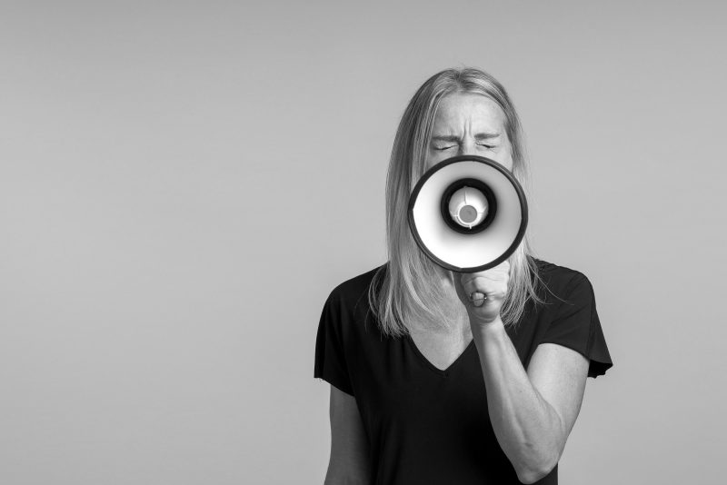 Angry Woman Yelling Into A Handheld Megaphone In A Concept Of Ac
