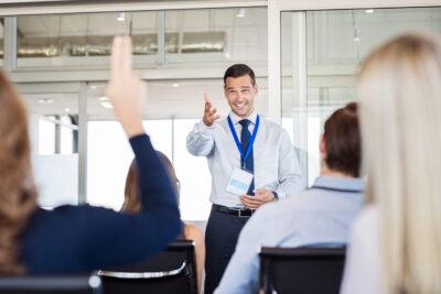 Businessman in seminar pointing towards woman raising hand to sa