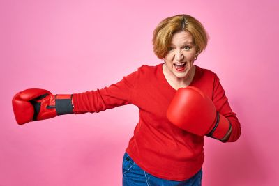 Woman Aged In Boxing Gloves. The Concept Of The Fight Against Ol