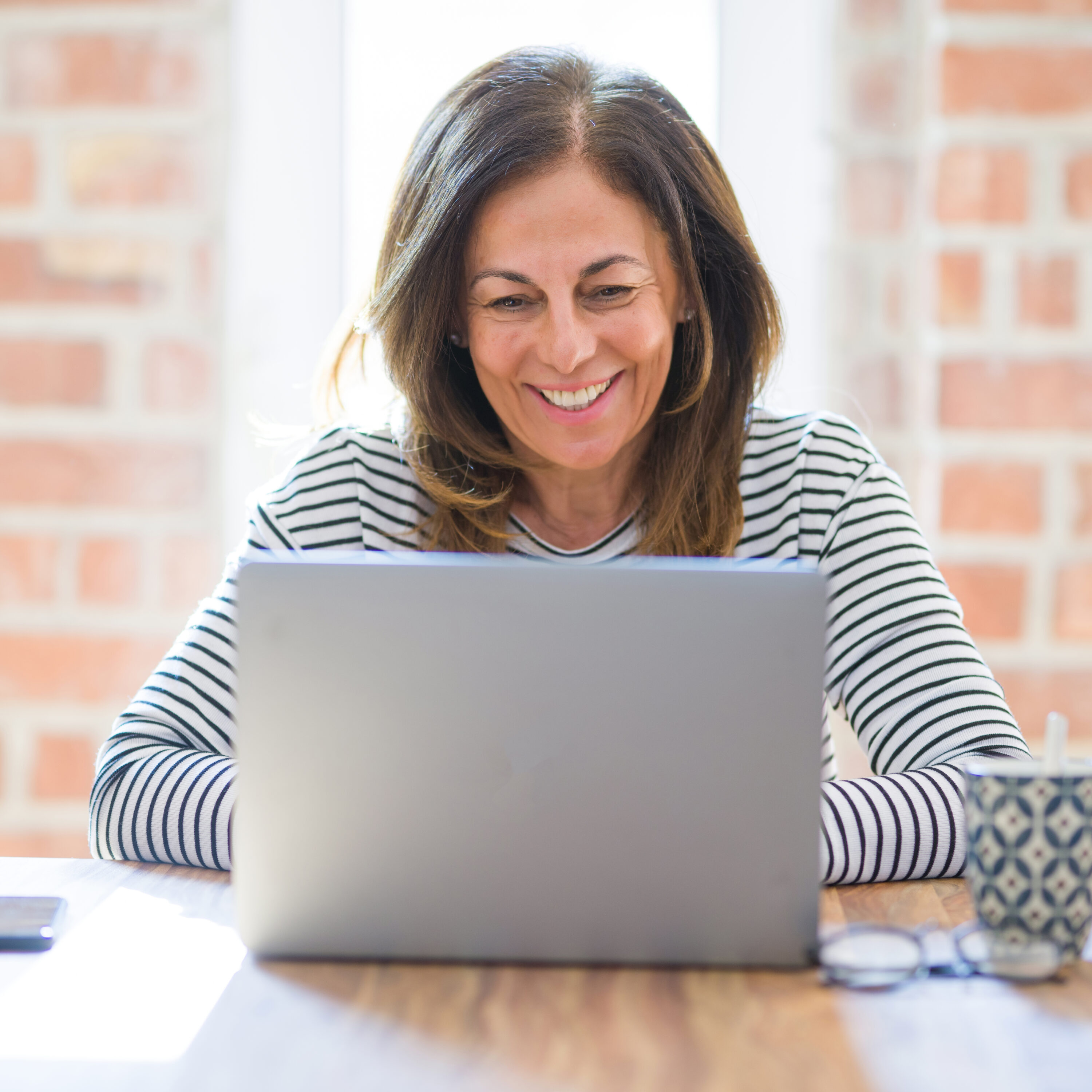 Middle age senior woman sitting at the table at home working usi