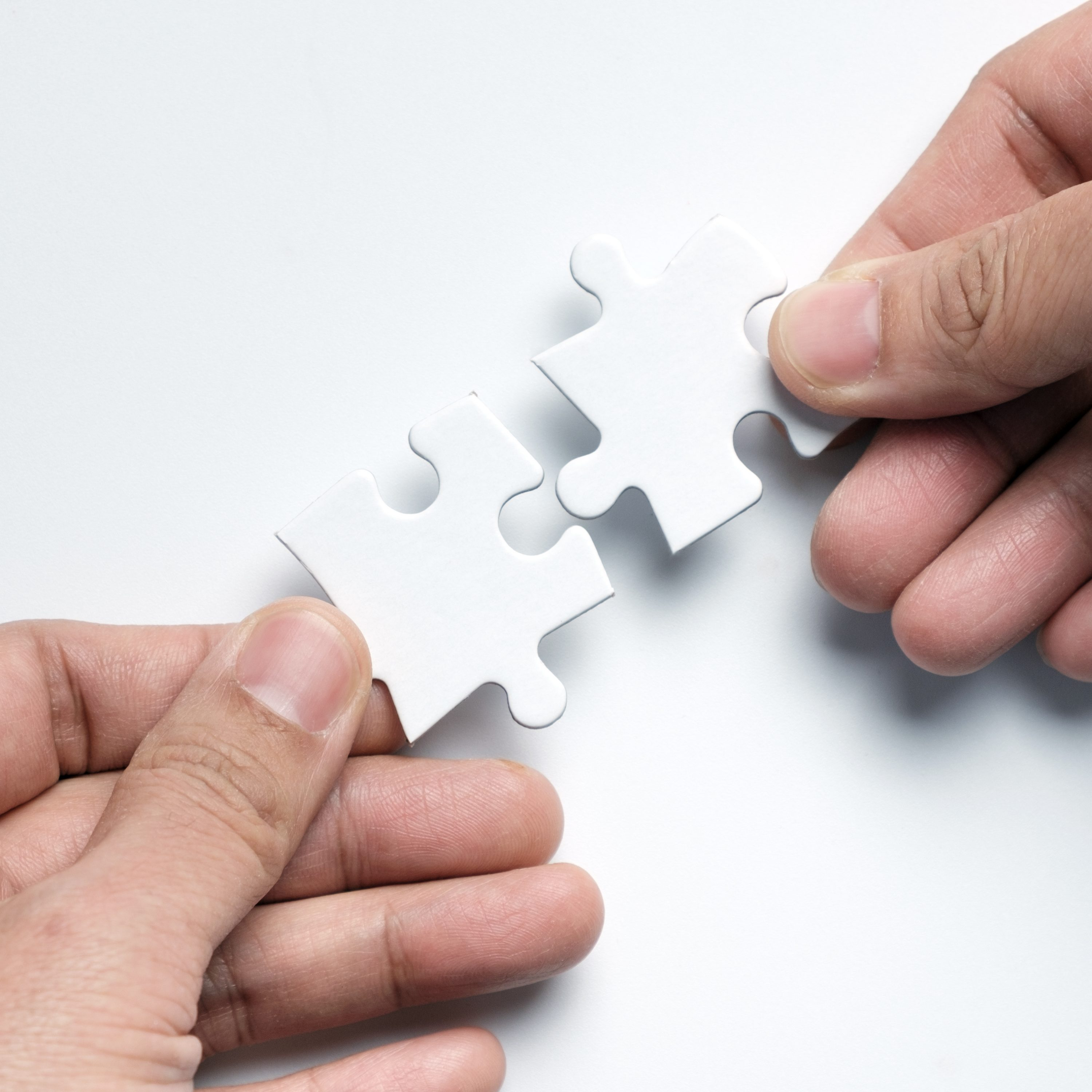 Partnership Concept With Hands Putting Puzzle Pieces Together On