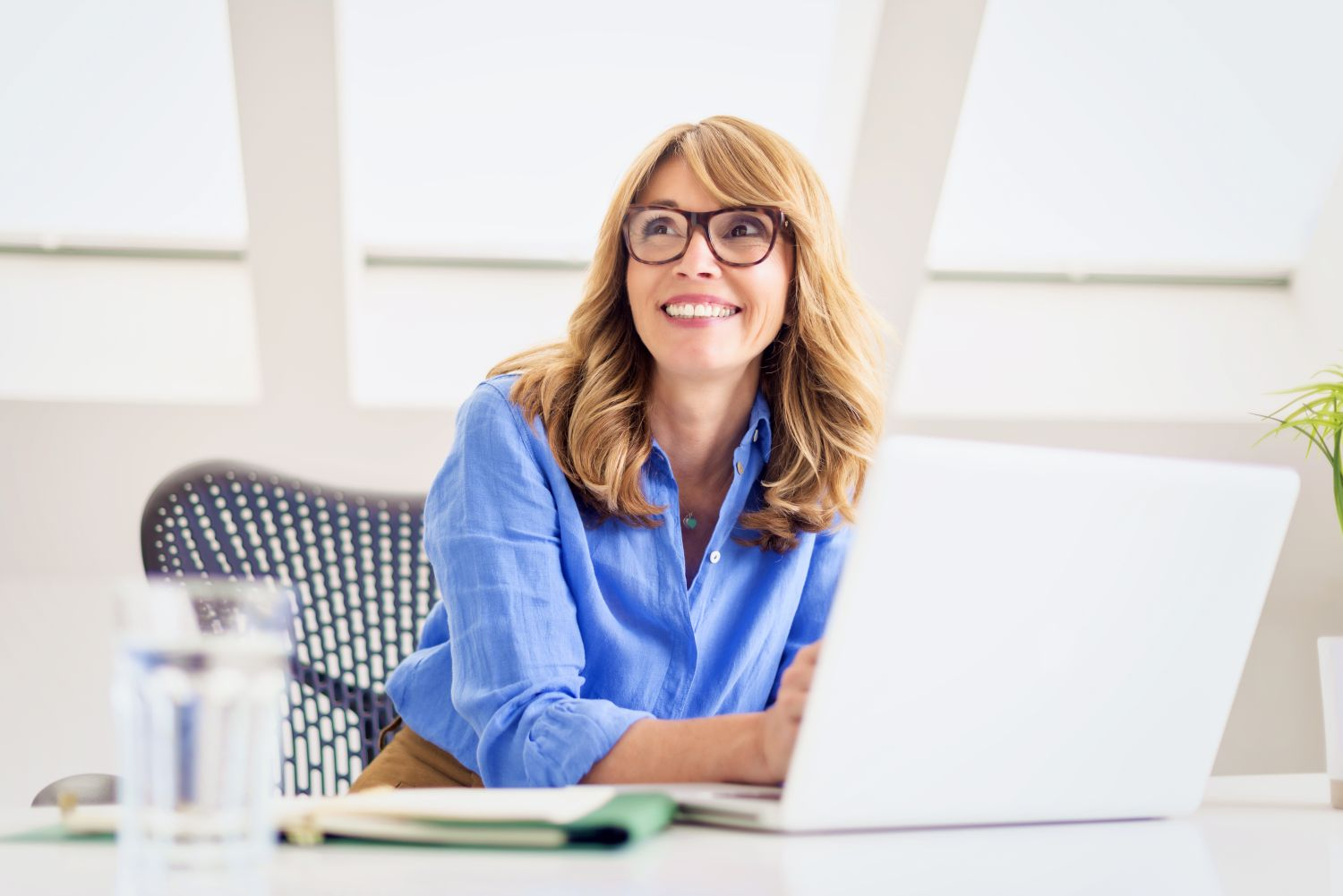 Shot Of Happy Mature Woman Sitting At Desk And Using Her Laptop